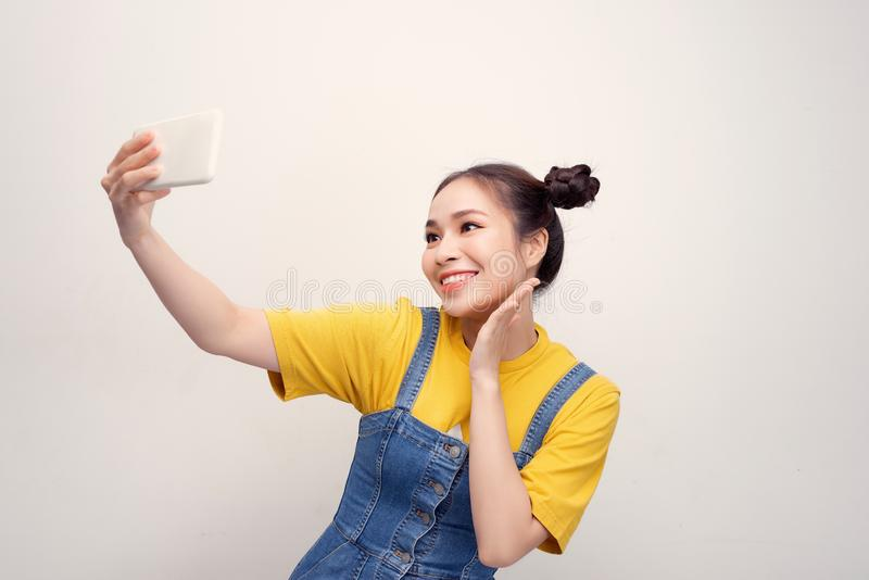 Young Asian woman wearing a jeans dungaree who taking selfie and smiling royalty free stock photos