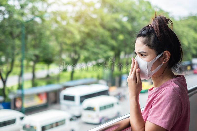 Young Asian woman wearing N95 respiratory mask protect and filter pm2.5 particulate matter against traffic and dust city. Healthcare and air pollution concept royalty free stock photo