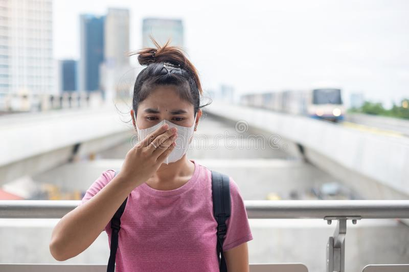 Young Asian woman wearing N95 respiratory mask protect and filter pm2.5 particulate matter against traffic and dust city. Healthcare and air pollution concept stock image