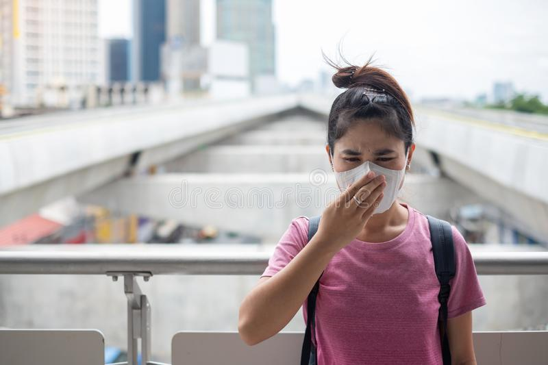 Young Asian woman wearing N95 respiratory mask protect and filter pm2.5 particulate matter against traffic and dust city. Healthcare and air pollution concept royalty free stock photography