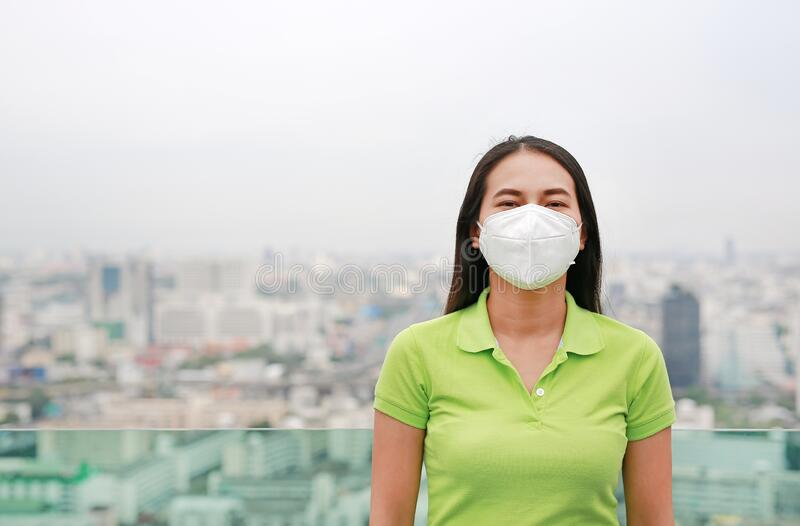 Young Asian woman wearing a protection mask against PM 2.5 air pollution in Bangkok city. Thailand. Reduce air pollution concept royalty free stock image