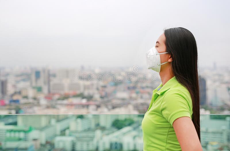 Young Asian woman wearing a protection mask against PM 2.5 air pollution in Bangkok city. Thailand. Reduce air pollution concept stock photos