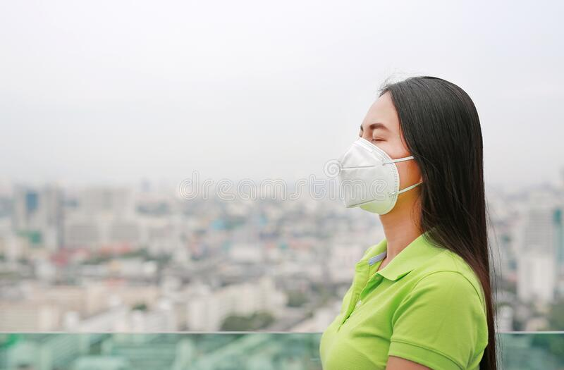 Young Asian woman wearing a protection mask against PM 2.5 air pollution in Bangkok city. Thailand. Reduce air pollution concept royalty free stock images