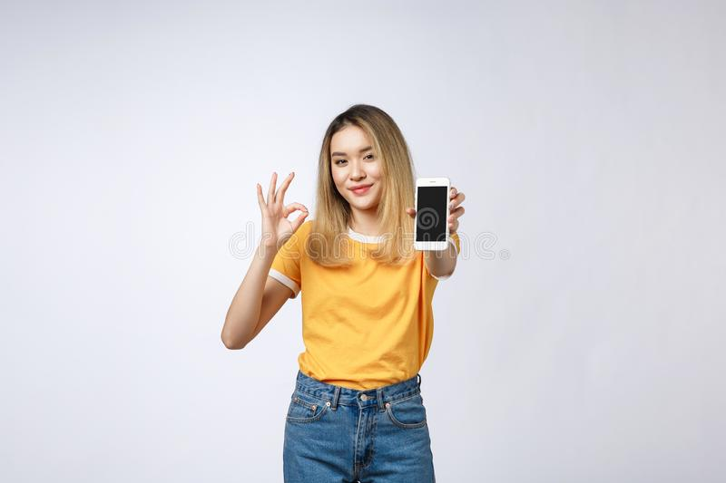 Young Asian woman wearing in yellow shirt is showing ok sign on white background, holding mobile phone, smiling, stock photos