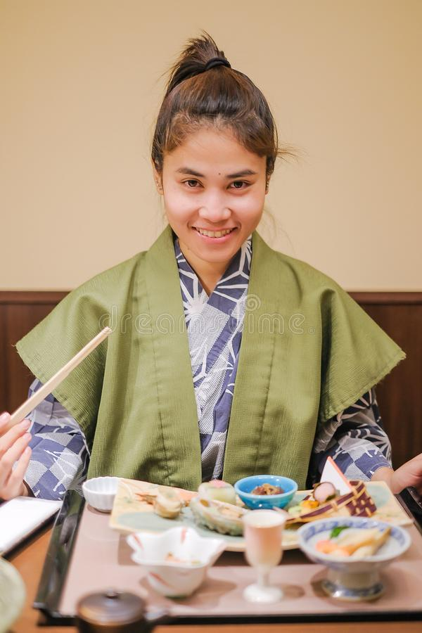 Young Asian woman wearing Yukata with Japanese Dinner set and appetizer on wooden table in Traditional ryokan resort at stock photography