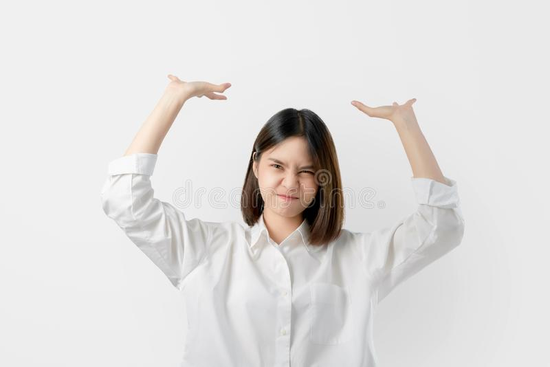 Young Asian woman in white casual clothes attempt to hold something heavy from above. royalty free stock photo