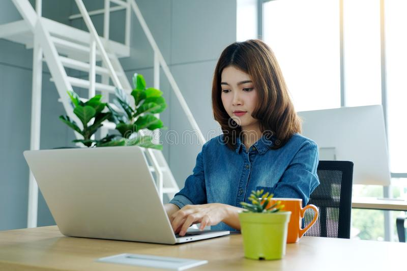 Young asian woman working with laptop computer at office with ha. Ppy emotion, working at home, office casual lifestyle concept stock photo
