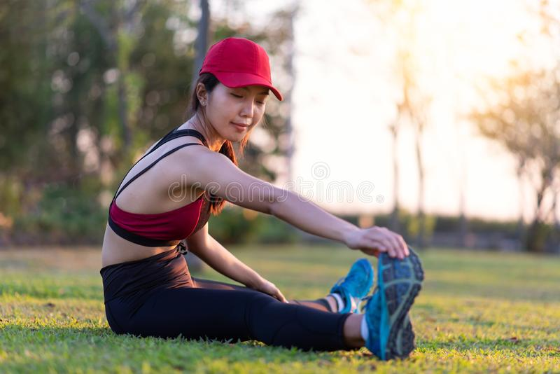 Young Asian woman working out and stretching legs in green park royalty free stock photography