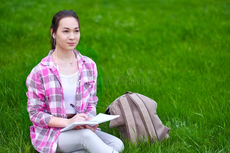 Young Asian woman writing in notebook seated on grass meadow royalty free stock photo