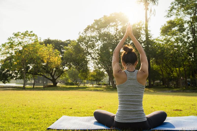 Young asian woman yoga outdoors keep calm and meditates while practicing yoga to explore the inner peace. Yoga and meditation have good benefits for health stock images