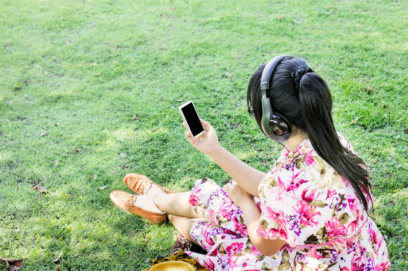 Young Asian women back or rare view listen to music via headphone sitting on grass field in park, women in pink flowers pattern d royalty free stock photo