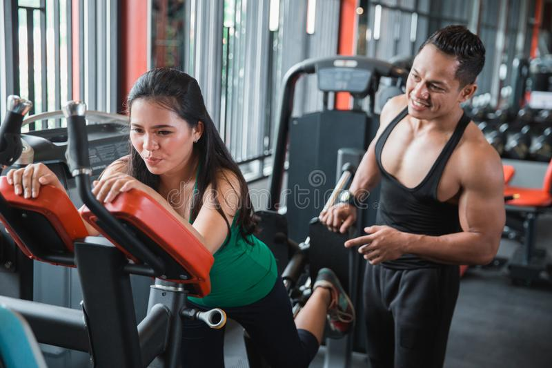 Young asian woman doing back leg presses royalty free stock photography