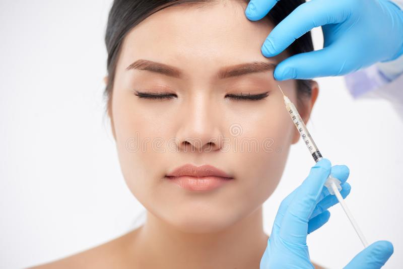 Beauty injection. Young Asian women getting rejuvenating botox injection under brow stock images