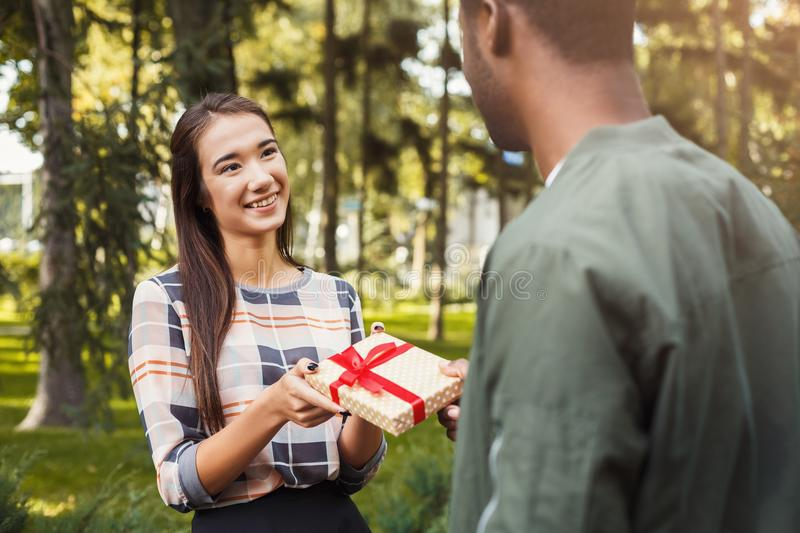 Man surprising his girlfriend with gift royalty free stock images
