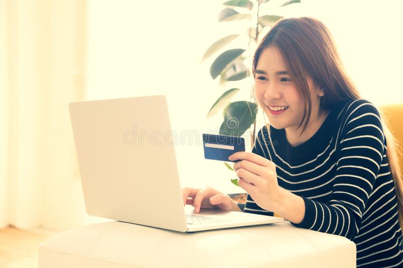 Young asian women holding credit card on hand for online shopping with laptop computer stock photography