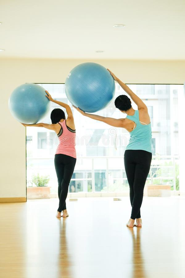 Young asian women practicing yoga ball, fitness stretching flexibility pose, working out, healthy lifestyle, wellness, well being royalty free stock photography