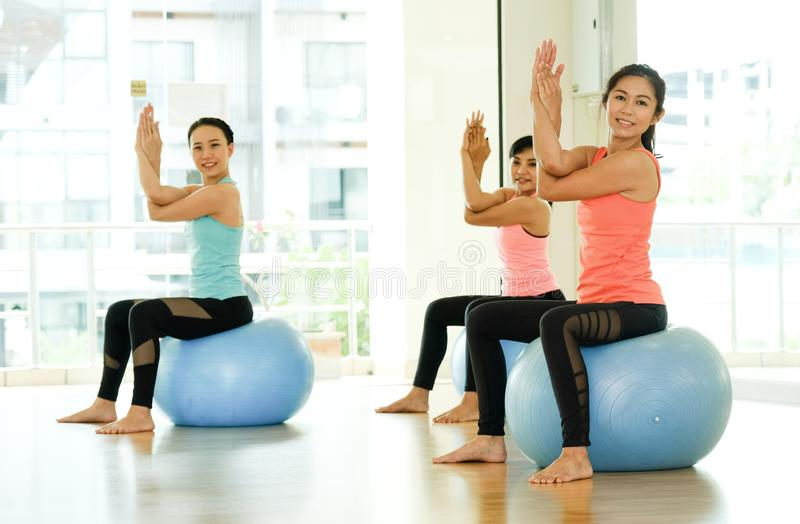 Young asian women practicing yoga ball, fitness stretching flexibility pose, working out, healthy lifestyle, wellness, well being stock photography