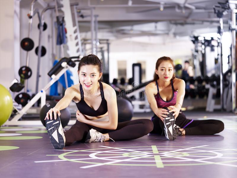 Young asian women stretching legs in gym. Young asian women stretching legs on the floor in modern gym looking at camera smiling stock photography