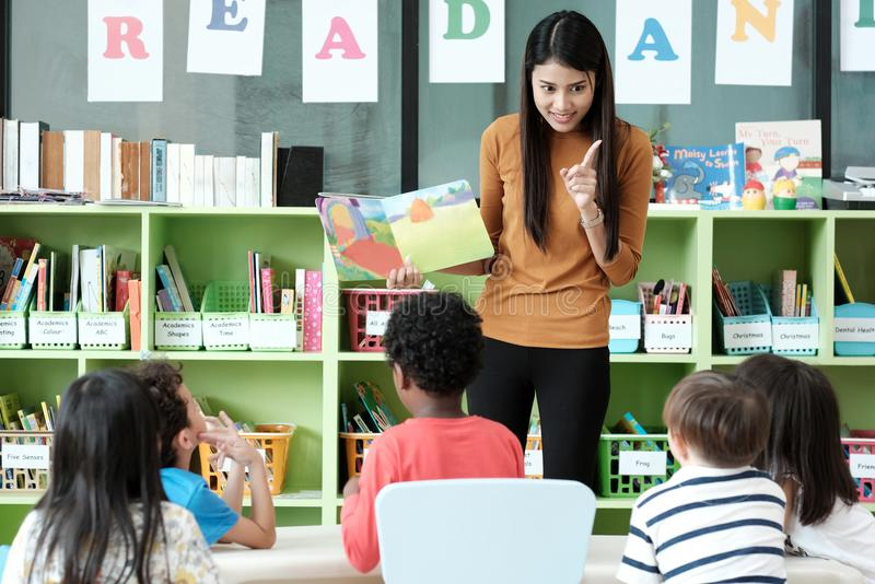 Young asian woman teacher teaching kids in kindergarten classroo royalty free stock photo