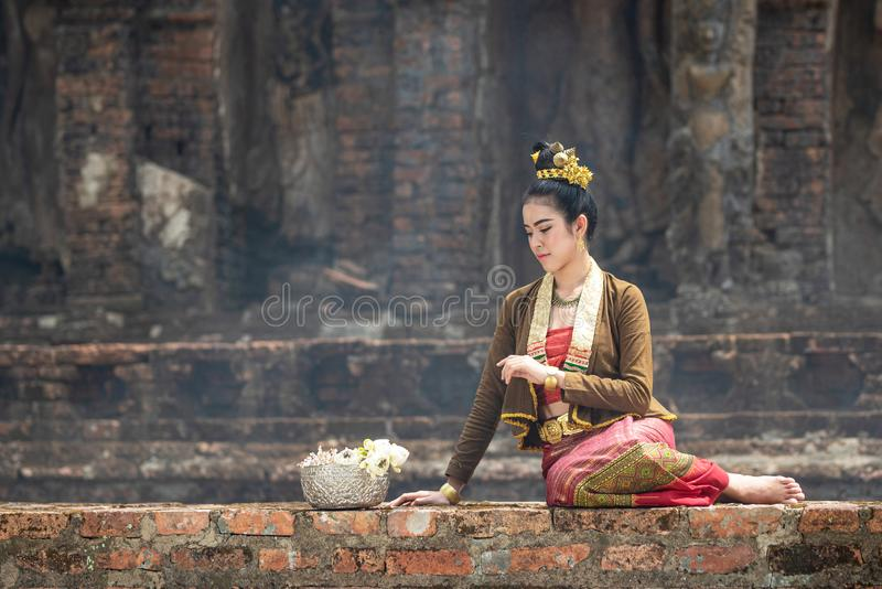 Young Asian women in Traditional dress sit on old wall look and silver bow ot lotus.Beautiful girls in traditional costume.Thai stock photo