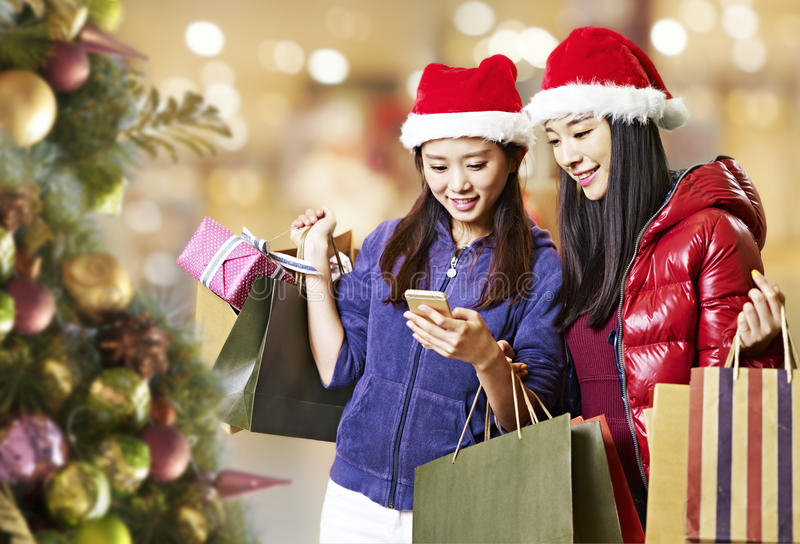 Young asian women using cellphone during christmas shopping stock image
