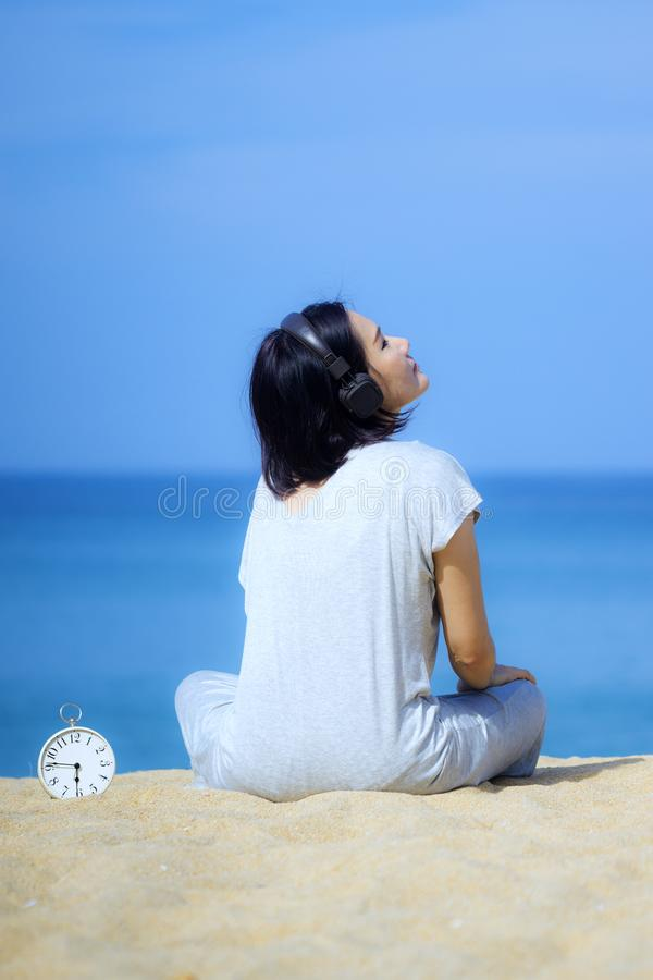 Young asian women wearing headphones, listening to music at the beach. White alarm clock placed on the sand. Blue sea and sky as a. Young asian woman wearing royalty free stock photography