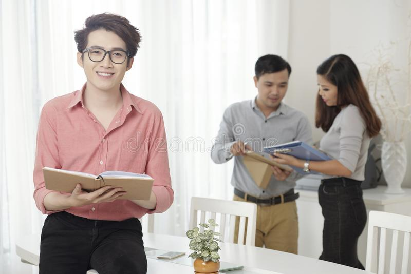 Young Asian worker with book and colleagues royalty free stock photo