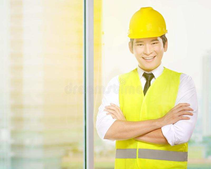 Young asian worker man in safety vest and yellow helmet standing in the office room. With skyscrapers background stock images
