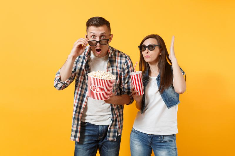 Young astonished couple woman and man in 3d glasses watching movie film on date holding bucket of popcorn and plastic royalty free stock images