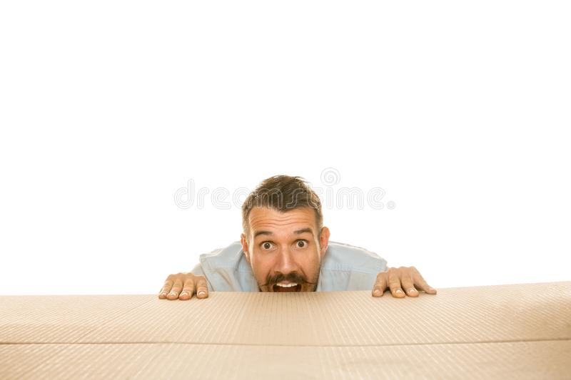 Young man opening the biggest postal package isolated on white. Young astonished man opening the biggest postal package isolated on white. Shocked male model on royalty free stock photo
