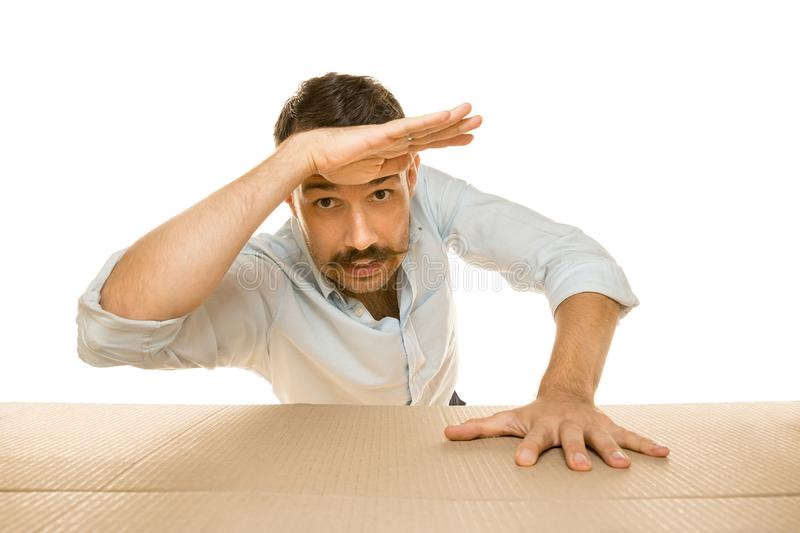 Young man opening the biggest postal package isolated on white. Young astonished man opening the biggest postal package isolated on white. Shocked male model on royalty free stock photography