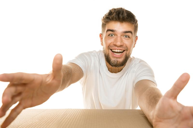Young man opening the biggest postal package isolated on white. Young astonished man opening the biggest postal package isolated on white. Shocked male model on stock photo