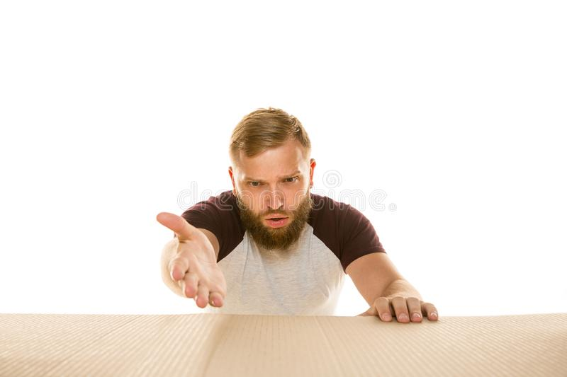 Young man opening the biggest postal package isolated on white. Young astonished man opening the biggest postal package isolated on white. Shocked male model on stock photography