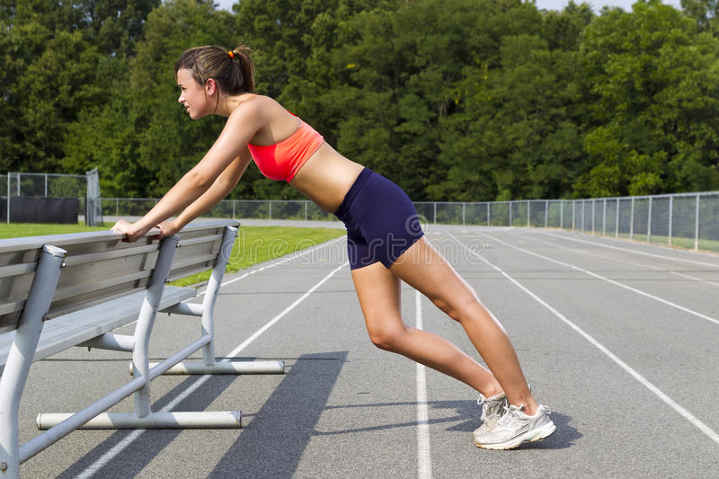 Young Athlete. An athletic teenager stretching before exercising on a track outdoors royalty free stock photos