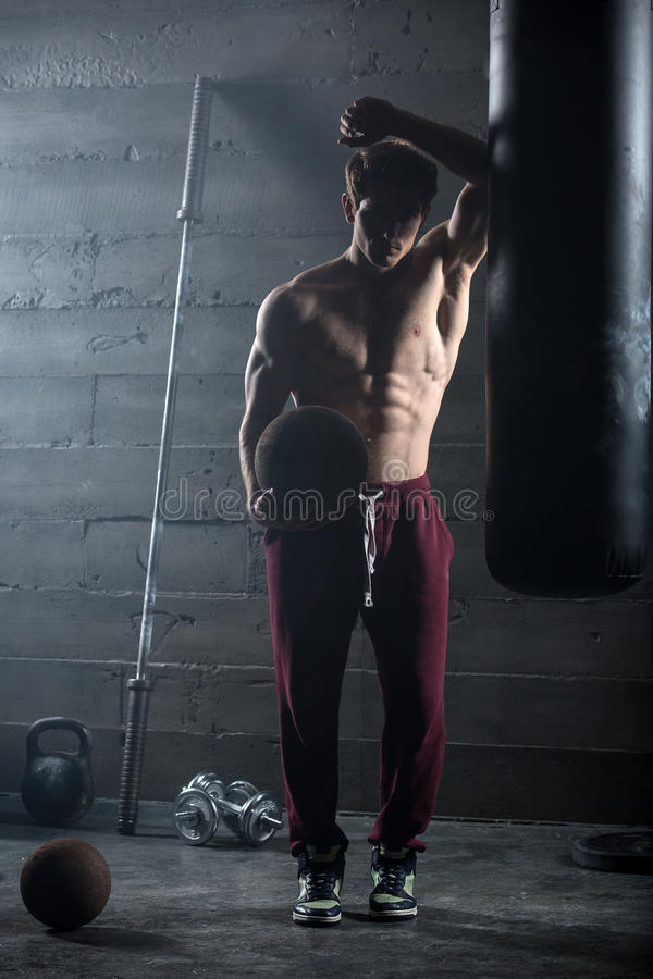 Young athlete with the ball in one hand. Stands near the punching bag. Snapshot in dark colors royalty free stock photo
