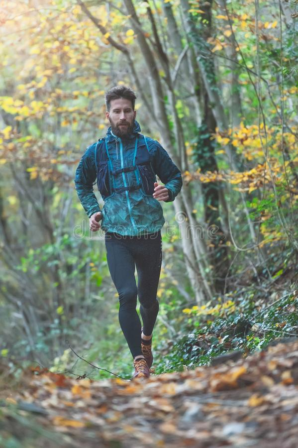 Young athlete with beard runs in the rain on a trail with technical clothing royalty free stock photos