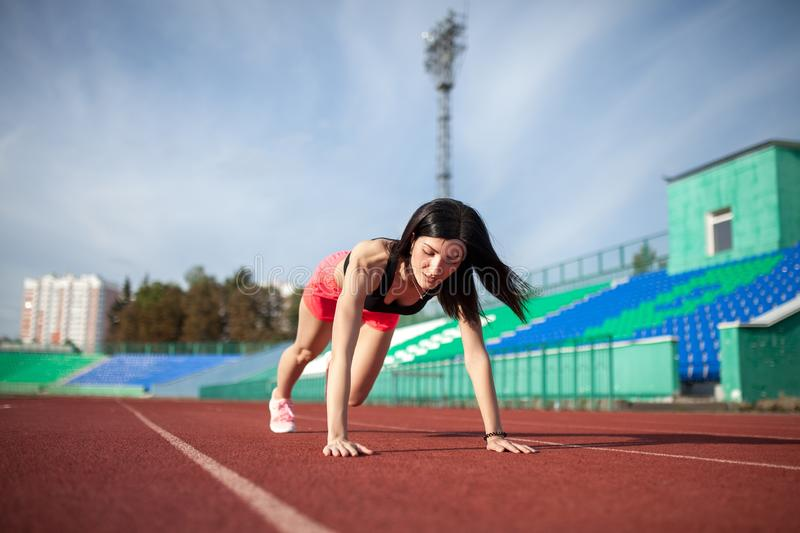 Young athlete brunette woman in shorts and tank top on stadium sporty lifestyle doing push ups on track looking aside concentrated royalty free stock photos