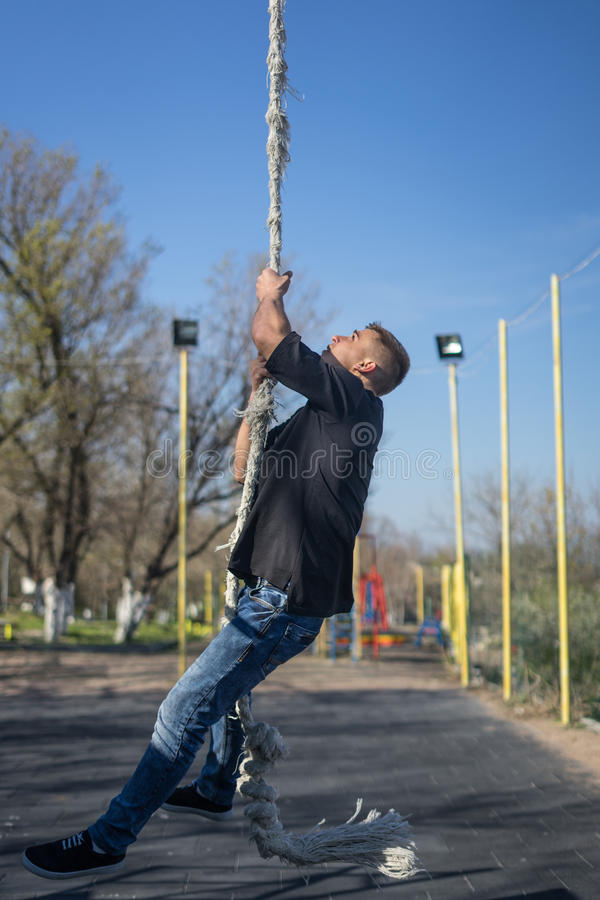 Young Athlete climbing up the Fitness rope royalty free stock image