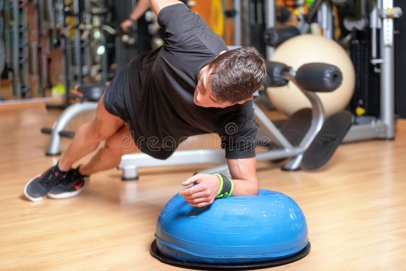 Young Athlete Doing Abs Exercise On Ball As Part Of Bodybuilding Training. stock photo