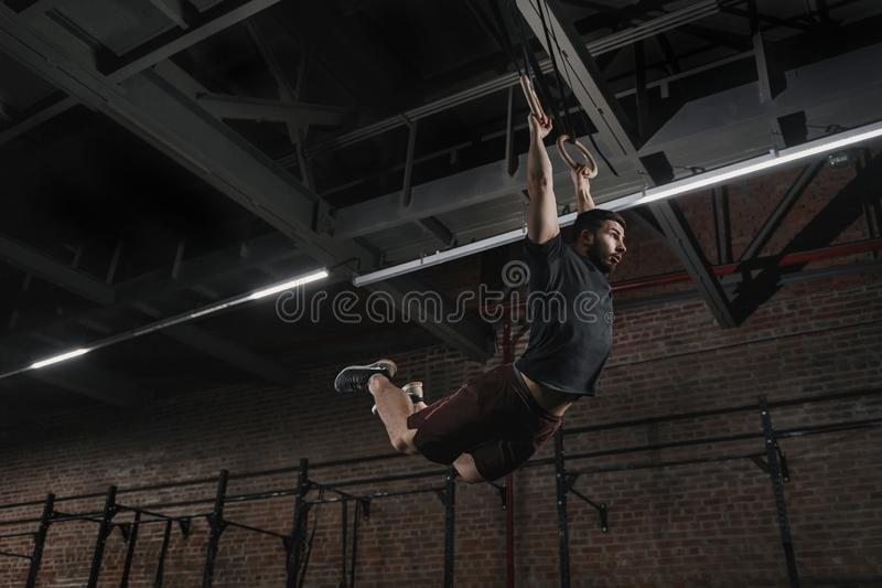 Young athlete doing pull-ups on gymnastic rings at the cross fit gym. Handsome man practicing muscle ups swinging workout exercise stock image