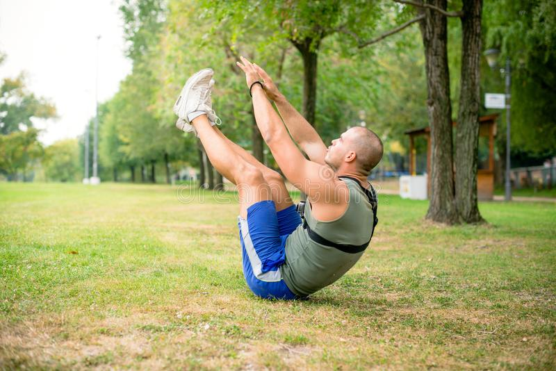 Young athlete exercising in public park stock photography