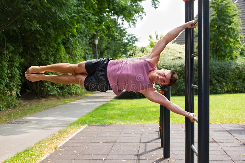 Young athlete having calisthenics flag workout:. Young man doing exercises on vertical bar outdoors in park, performing human flag figure stock photos