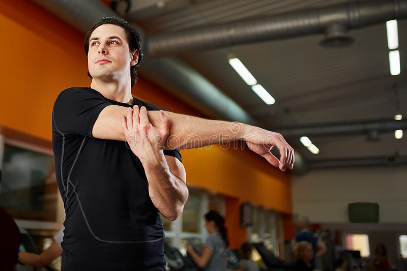 Young athlete healthy man in the black sportwear stretching shoulder before gym workout. royalty free stock photos