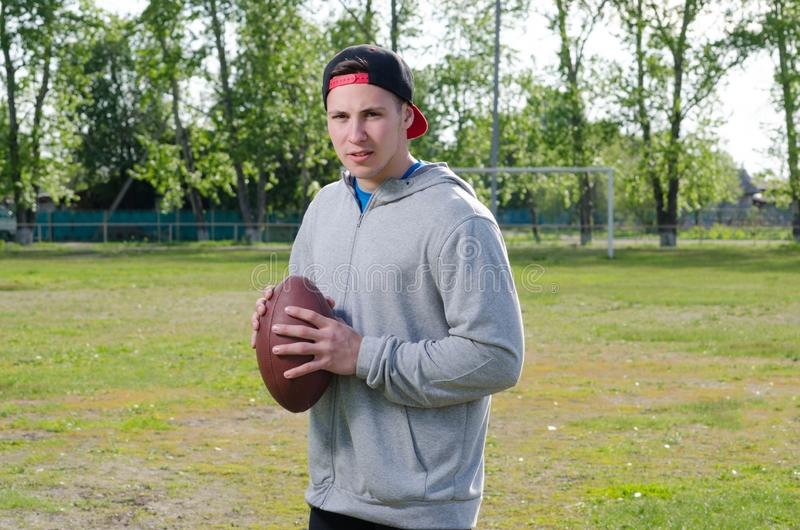 Young athlete holding a football ball stock photography