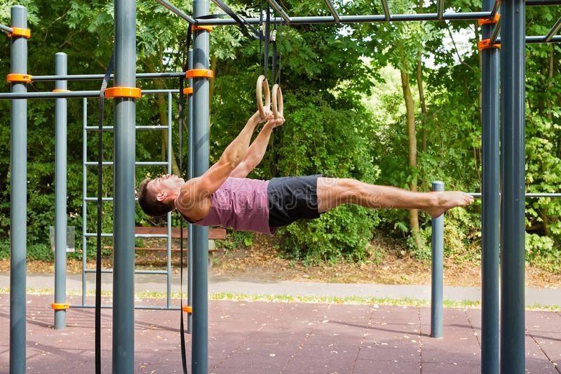 Handsome young man doing calisthenics ring workout:. Young athlete in horizontal position hanging on rings doing exercises during calisthenic training outdoors stock photo
