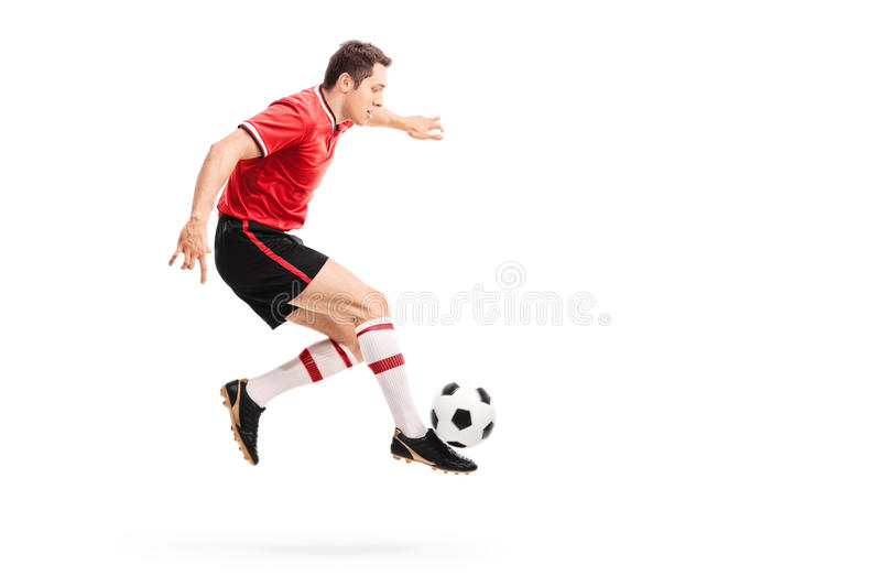 Young athlete jumping and kicking a football stock image