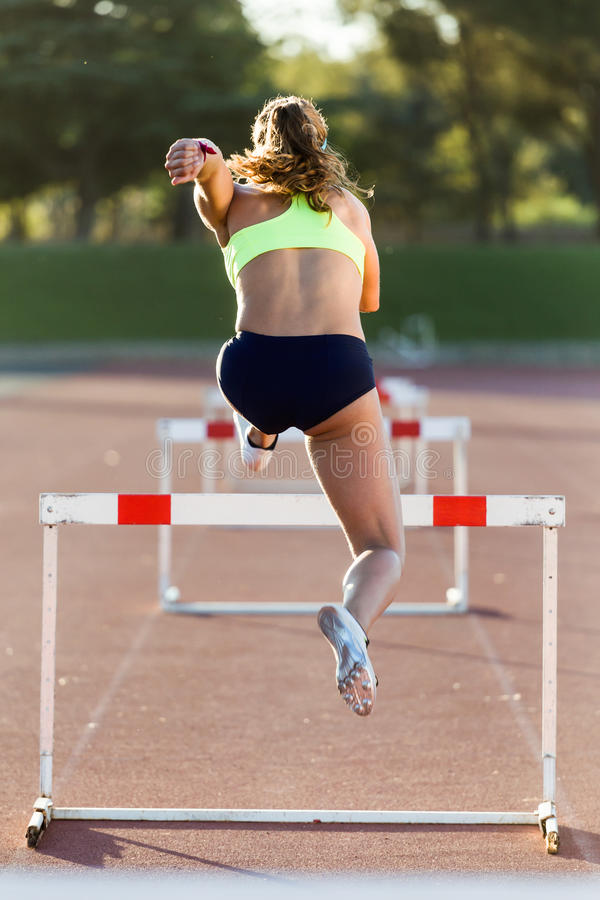 Young athlete jumping over a hurdle during training on race trac. Portrait of young athlete jumping over a hurdle during training on race track royalty free stock photos