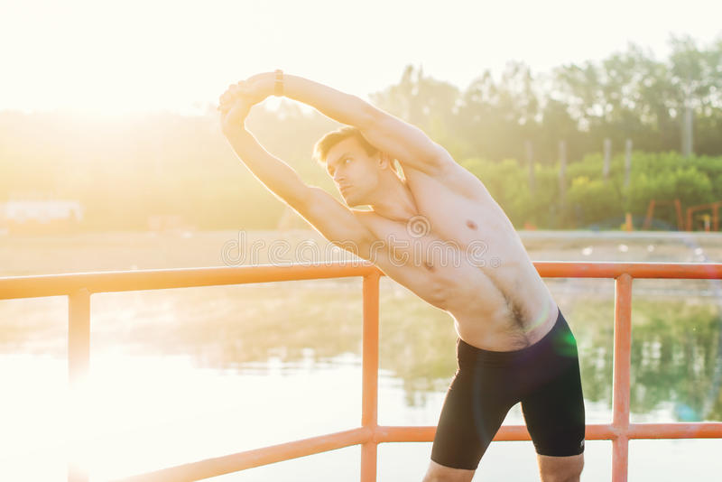 Young athlete man doing side bend exercise. stock photos