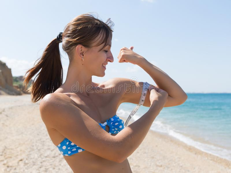Girl is measuring with a tape measure biceps on seashore stock image