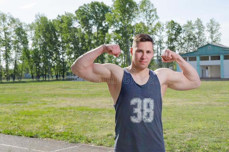 Young athlete shows biceps royalty free stock photo